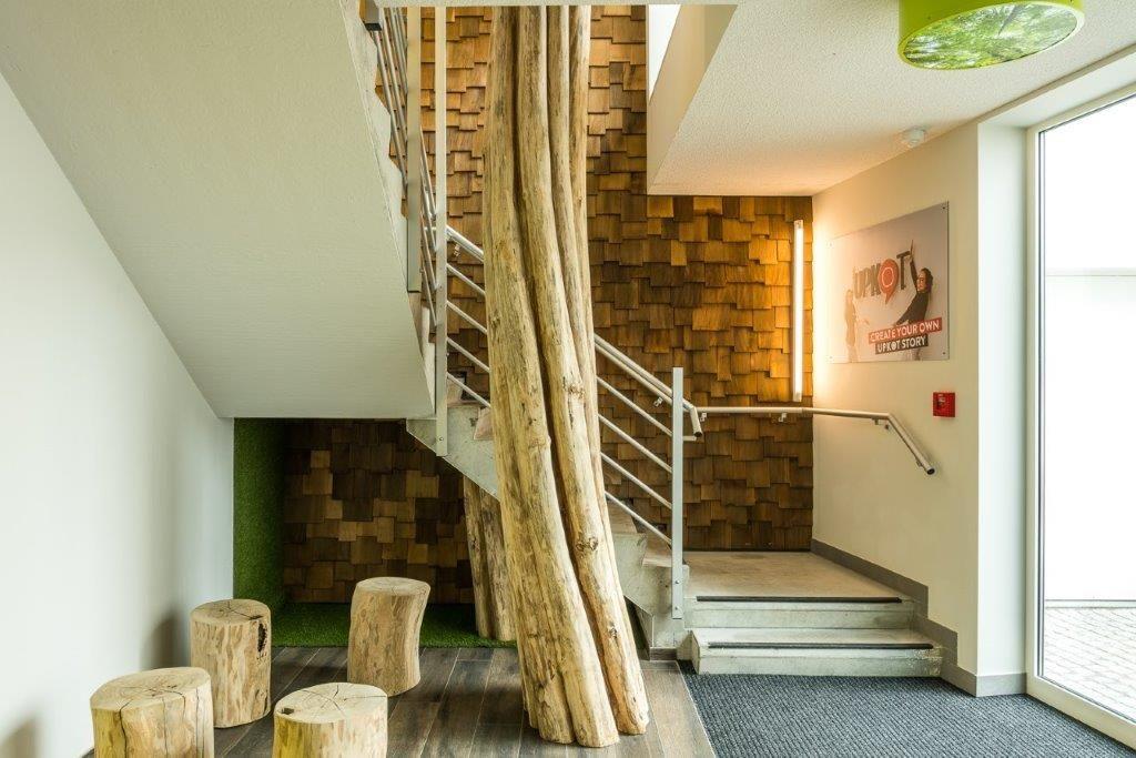 De lay-out met houten shingles en de boomstammenrij loopt door tot in de inkomhal. (Beeld: Luc Roymans)