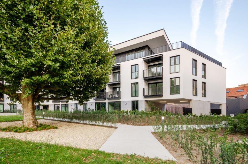 De sokkel van het appartementsgebouw is bekleed met grijze natuursteen, terwijl de gevels van de eerste en de tweede verdieping zijn afgewerkt met witte buitenbepleistering.