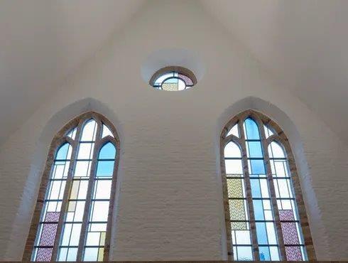 De glas-in-loodramen zijn hersteld en kregen een eigentijdse artistieke invulling. (Beeld: Artes Woudenberg)