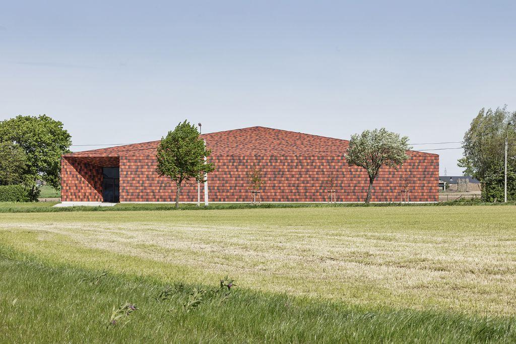De gevels en hellende dakvlakken zijn uniform bekleed zijn met bruinrode kleipannen, die zich naadloos inpassen in het agrarische landschap. (Foto: Piet-Albert Goethals)