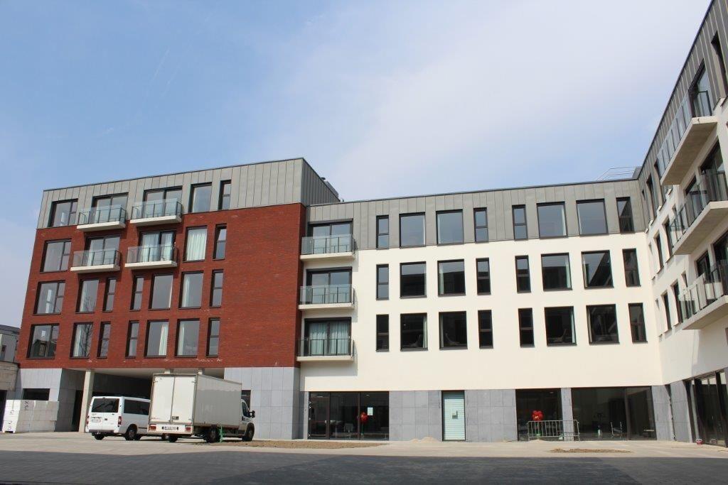 De eerste verdieping fungeert als het ware als sokkel en is bekleed met blauwe steen, terwijl de bovenliggende niveaus afgewerkt zijn met witte gevelpleister, gevelmetselwerk of zink (kopvolumes).