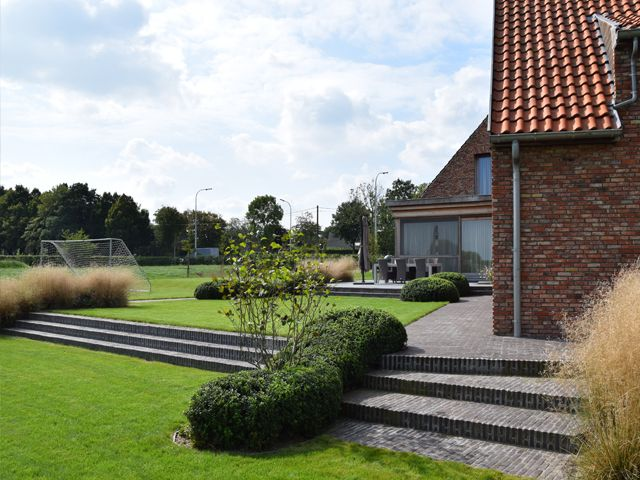 Landschapstuin met kleiklinkers vervolmaakt gerenoveerde vierkantshoeve