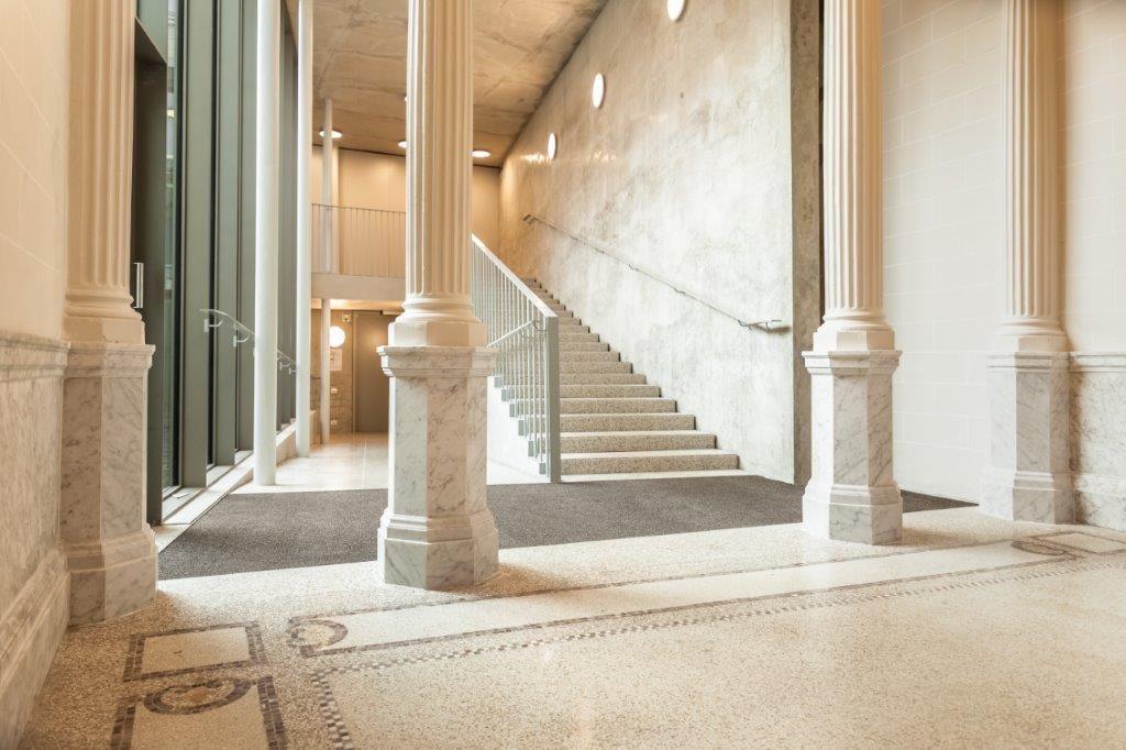 In het nieuw aangebouwde gedeelte achter de zuilenpartij is een 'luie' trap geplaatst. Die overbrugt de zachte helling die resulteert uit het niveauverschil in de drie gebouwen.