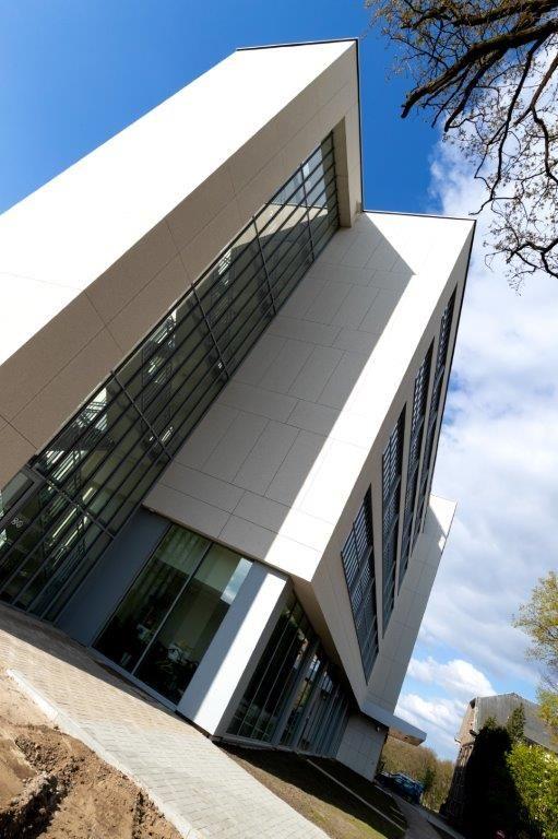 De oorspronkelijke uitstraling van het gebouw is maximaal bewaard: grote raampartijen, lichte gevelplaten en een zuidgevel in metselwerk. (Beeld: Eddy Vanoppen (Fotomakers) – Willemen Construct)