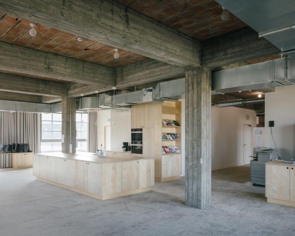 De industriële sfeer en materialiteit van het gebouw zijn maximaal bewaard en aangevuld met fraaie houtaccenten.