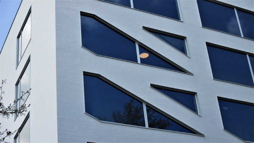 In de betonnen oostgevel van de lestoren zijn tal van kleine driehoekige ramen geïntegreerd.