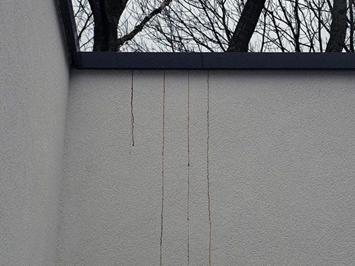 Verschijning van bruinkleurige afdruipsporen door condensatievorming ter hoogte van de muurkappen.