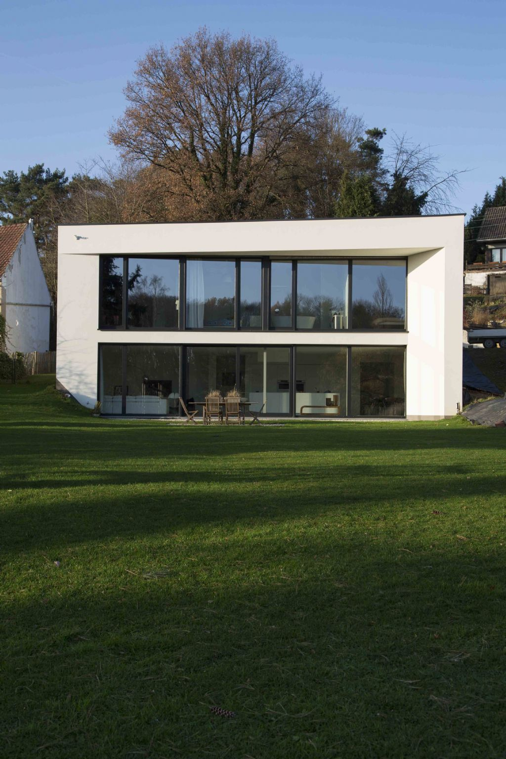 Villa minimaliste dont la volumétrie est dictée par les limites parcellaires obliques et le souci d'avoir un impact minimal sur l'étroite voirie publique.