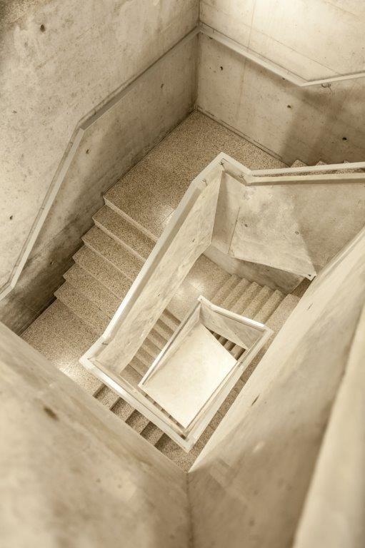 Een trappenhal in zichtbeton vormt de overgang tussen oud en nieuw en verbindt de drie gebouwen.