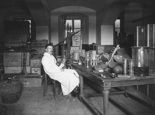 Jean Swinnens aan het werk in de kelders van het museum. Hij ontsmette en restaureerde binnengekomen objecten.
