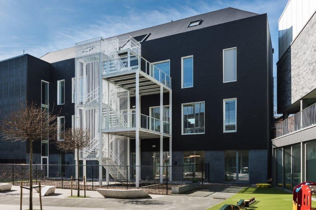 Het volume van het bestaande gebouw bleef ongewijzigd. De buitenschil is volledig geïsoleerd en afgewerkt met keramische dak- en gevelpannen. (Beeld: Yoni De Mulder)