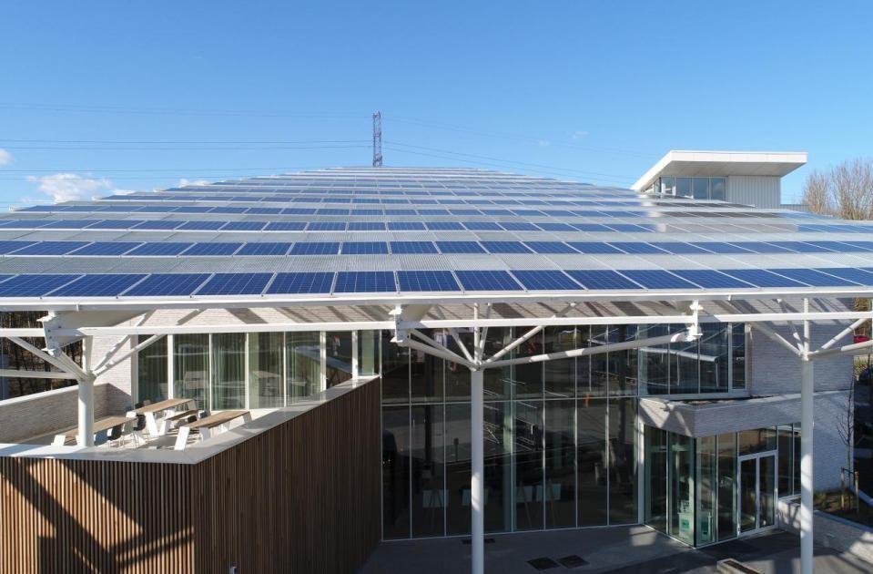 De stalen luifel aan de buitenzijde van het gebouw vervult drie functies: architecturale eyecatcher, drager voor de PV-panelen en zonwering van de achterliggende zuidgevel. (Beeld: Confederatie Bouw Limburg)