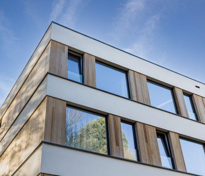 Tussen de langgerekte stroken in wit pleisterwerk, die lijken te zweven dankzij de aanwezigheid van uitkragende terrassen op de kop van het gebouw, maken vooral hout en glas de dienst uit.