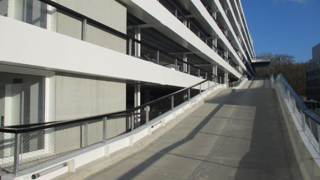 De randbalken zijn uitgevoerd in beton en bekleed met een wit plaatmateriaal, wat in combinatie met de witte staalelementen en de slanke zwarte leuningen een strakke uitstraling oplevert.