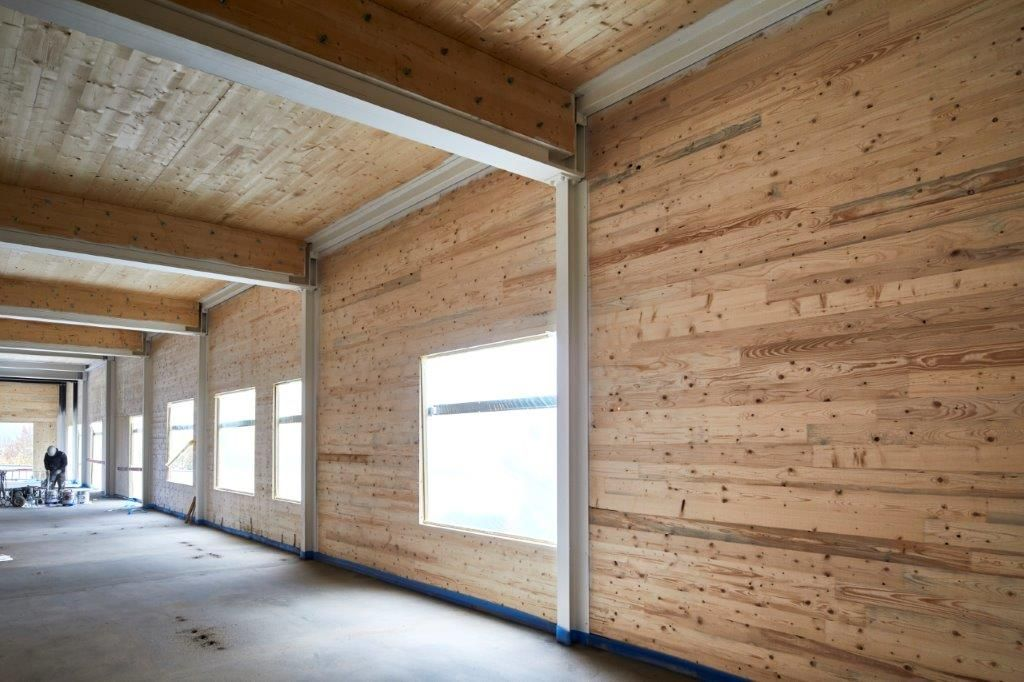 De staalstructuur is aan de hand van gecombineerde draagliggers in hout en staal ingevuld met CLT-wanden en -vloeren.