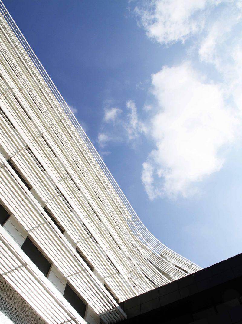 Op de gestripte betonnen constructie werd een dikke laag isolatie aangebracht met daarover een witte aluminium gevelbekleding.