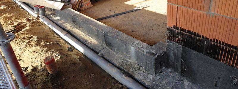 Bescherming van de muurvoet door middel van een membraan met gelaste naden.
