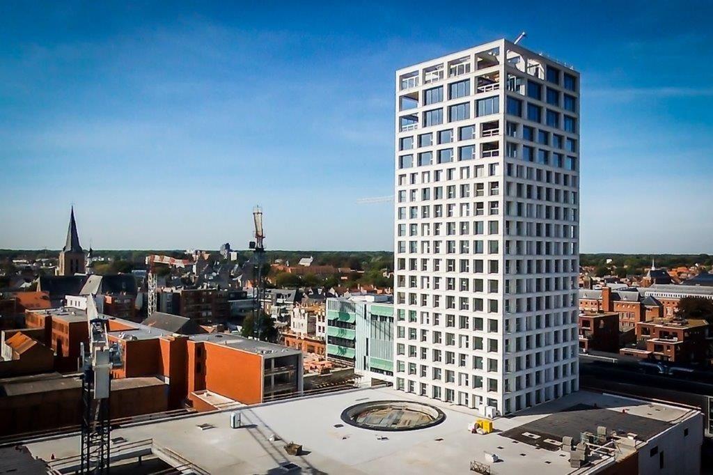 De gevels van de Turnova-toren bestaan volledig uit wit gezuurd architectonisch beton. Een hedendaagse verwijzing naar de witte natuursteen van het stadhuis aan de Grote Markt. (Beeld: Stefaan Van der Veken)