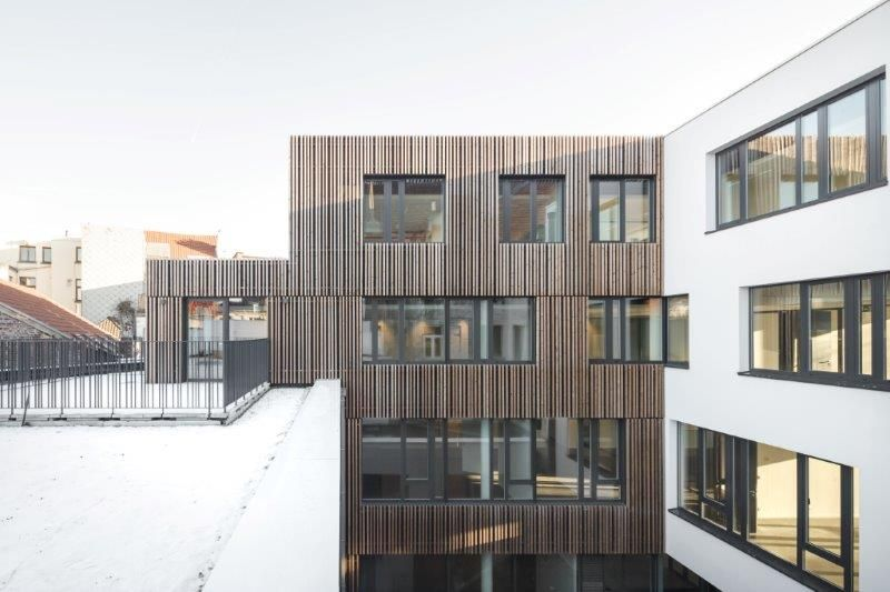 Sommige façades zijn afgewerkt met witte buitenbepleistering, wat resulteert in een interessant visueel contrast met de verticale houten balken. (Foto: Stijn Bollaert)