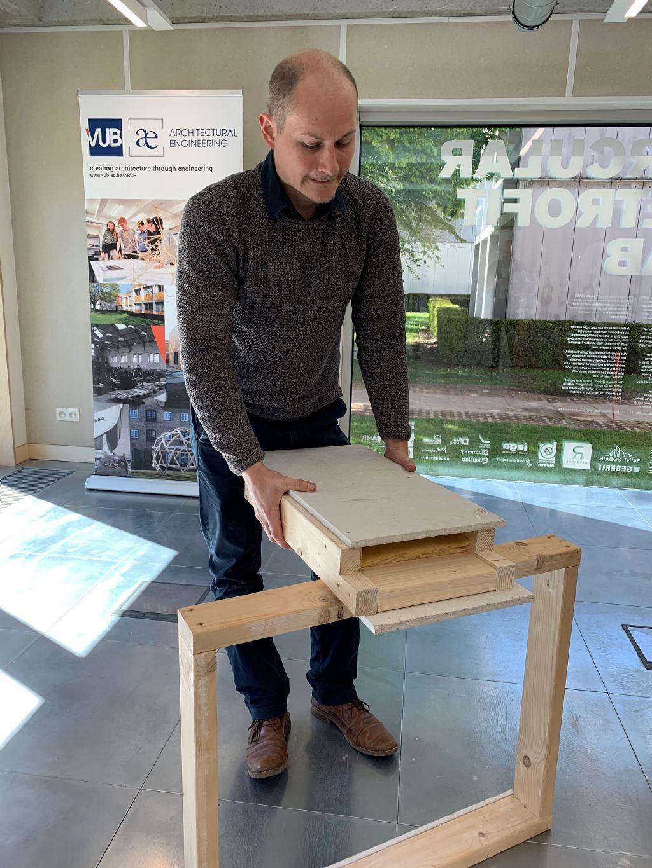 """Jeroen Poppe van het team rond prof. De Temmerman toont één van de vier gebruikte wandsystemen. """"Niet meer dan een houten kader waarin geprefabriceerde blokken met isolatie met een man/vrouw-verbinding geplaatst worden."""""""