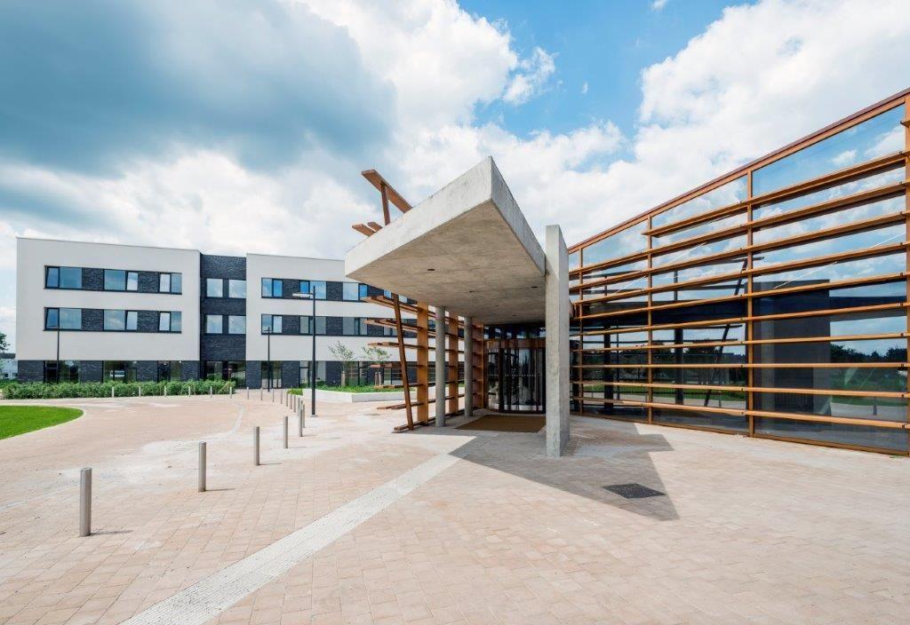 De ziekenhuisblokken zijn met elkaar verbonden via een transparante inkompartij. (Foto: Marc Sourbron)