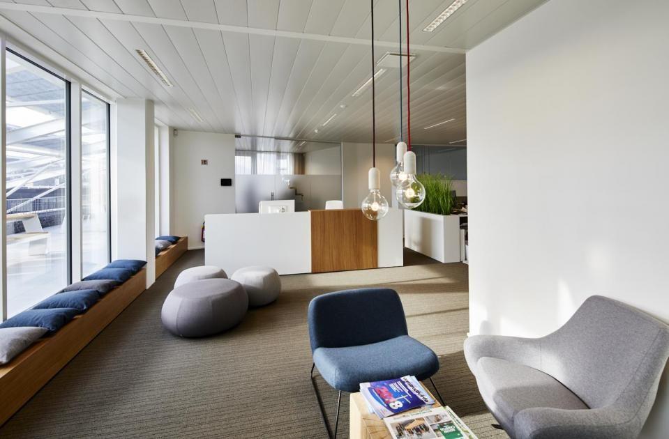 """Merlijn van Kan: """"De combinatie van warme elementen (eiken tafel, stijlvolle lampen …) en zakelijk-functionele elementen (verstelbare bureaus, kwalitatieve stoelen …) werkt uitstekend."""" (Beeld: Confederatie Bouw Limburg)"""
