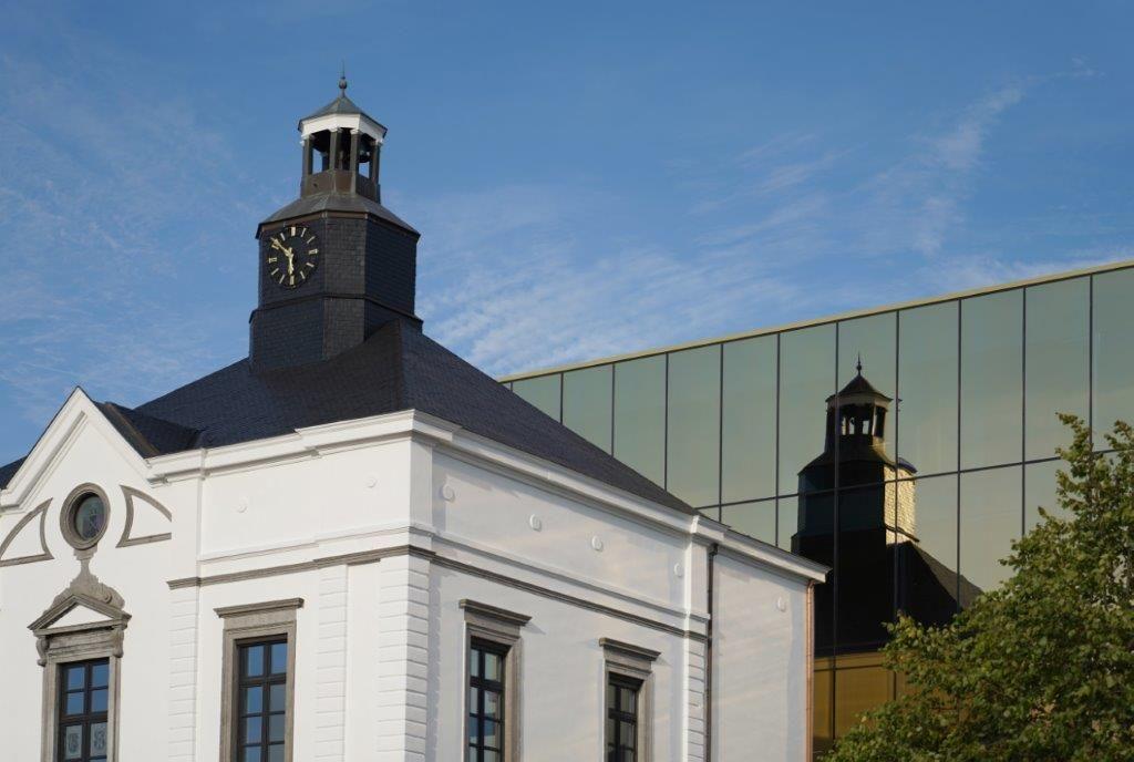 Het historische gedeelte wordt op een prachtige manier weerspiegeld in de vliesgevel van de nieuwbouw. (Beeld: Philippe Van Gelooven)