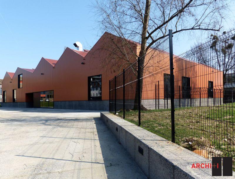 De gevel en het dak zijn bekleed met een koperkleurig gelakte staalplaat die de link moet leggen met de ambachten.