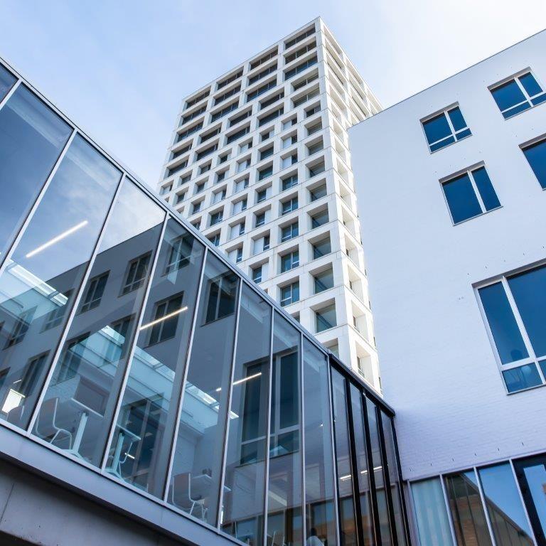 Het gelijkvloers en de eerste verdieping zijn voorbehouden voor commerciële ruimtes en een bankkantoor. In die 'winkelsokkel' is tevens een uniek beglaasd atrium geïntegreerd. (Beeld: Stefaan Van der Veken)
