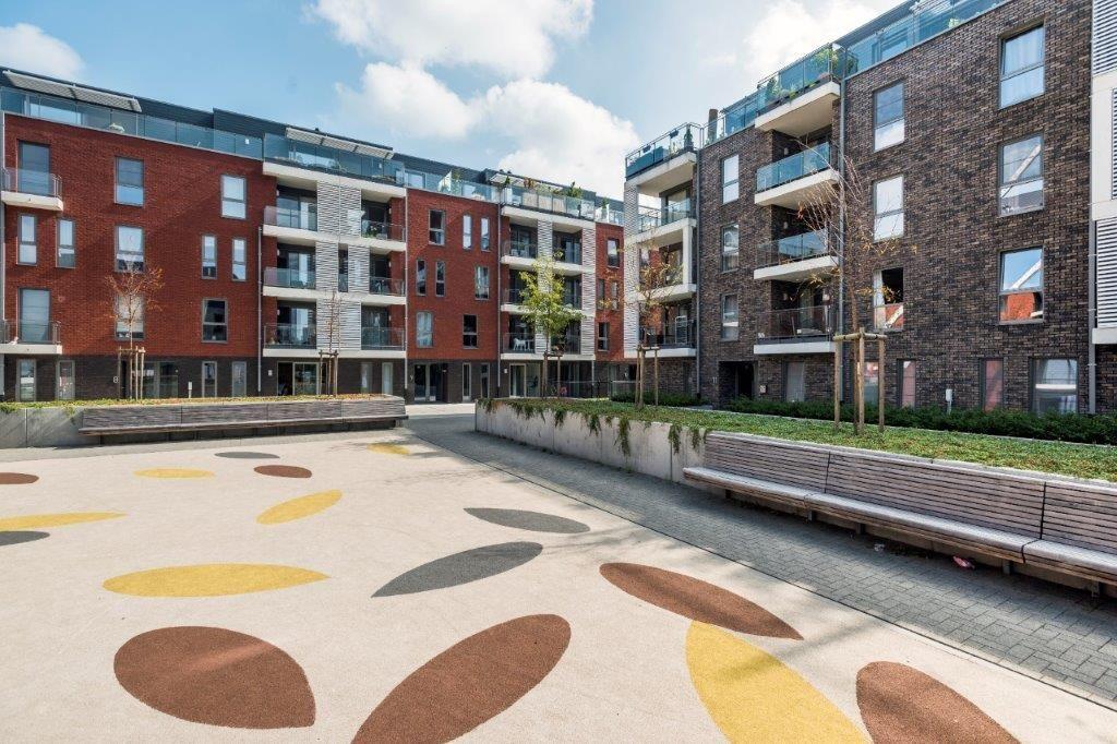 Het verkeersvrije Heldenplein is omzoomd met bomen en garandeert een aangename woonbeleving. Op de vloer zijn tekeningen van mout aangebracht. (Beeld: Marc Sourbron)