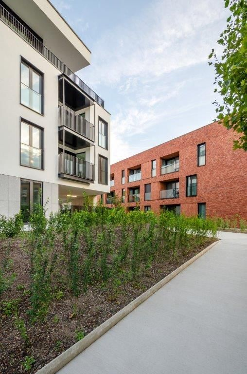 Het L-vormige appartementsgebouw toont een heel ander gelaat dan het assistentiewoningencomplex.