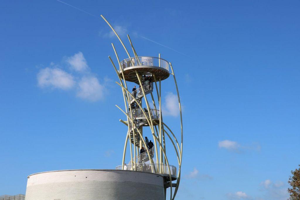Op de behouden bakstenen sokkel groeit de uitkijktoren, als een bundel duingras, spelend in de wind.