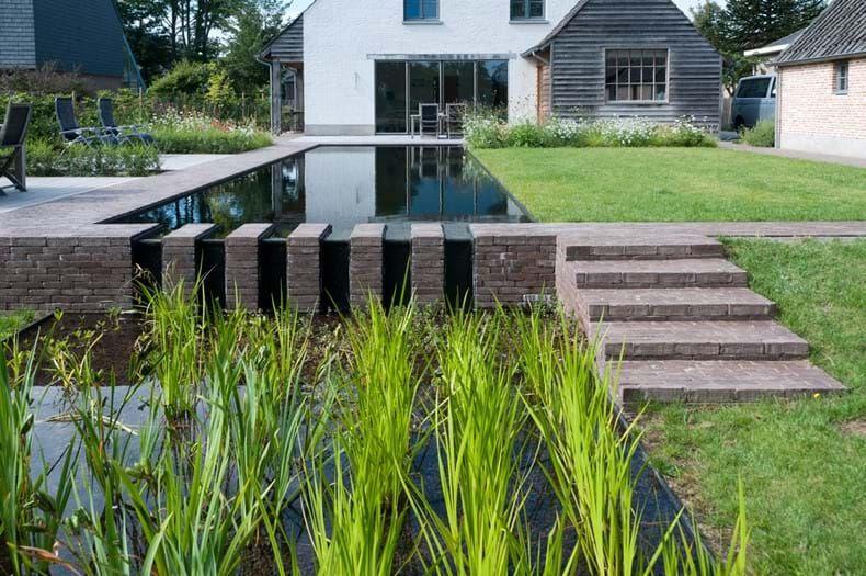 Zwemvijver omringd door kleiklinkers als schakel tussen tuin en landschap