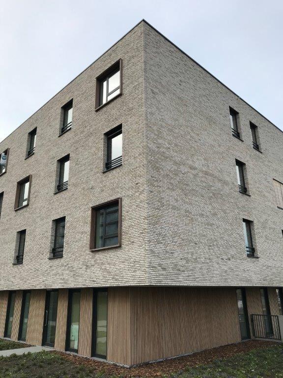 Het balkvolume is bekleed met neutraal ogende, witgrijze bakstenen die de massa van de constructie maximaal beperken en een verlichtend contrast met de omliggende bebouwing genereren. (Foto: a33 architecten)