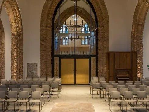 Het sacrale en het culturele gedeelte zijn van elkaar gescheiden aan de hand van opendraaibare messingpanelen in brandwerend stalen schrijnwerk. (Beeld: Artes Group)