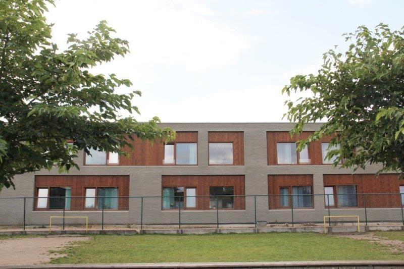 Het gebouw oogt eerder sober aan de buitenkant. De kleuren zijn van de gevel zijn gebaseerd op de Kempische vegetatie en zandgronden. (Foto: Van Belle & Medina Architects)