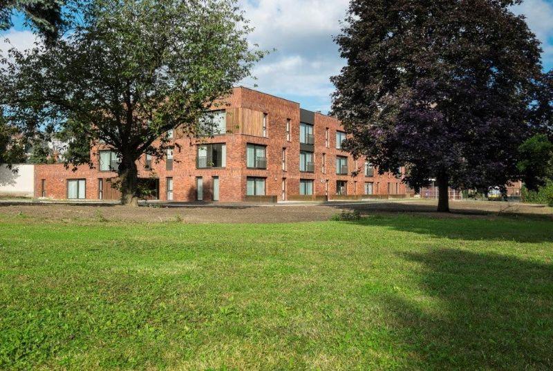 Het hoofdvolume bevindt zich aan de rand van een grote groene binnentuin.