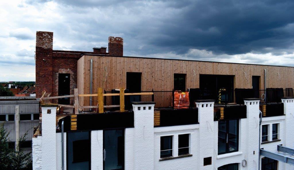 De nieuwe elementen creëren geen bezwarend contrast. Niets doet vermoeden dat er boven op het bestaande gebouw een houtskeletstructuur geplaatst is in functie van de duplexappartementen. (Beeld: Imoya)