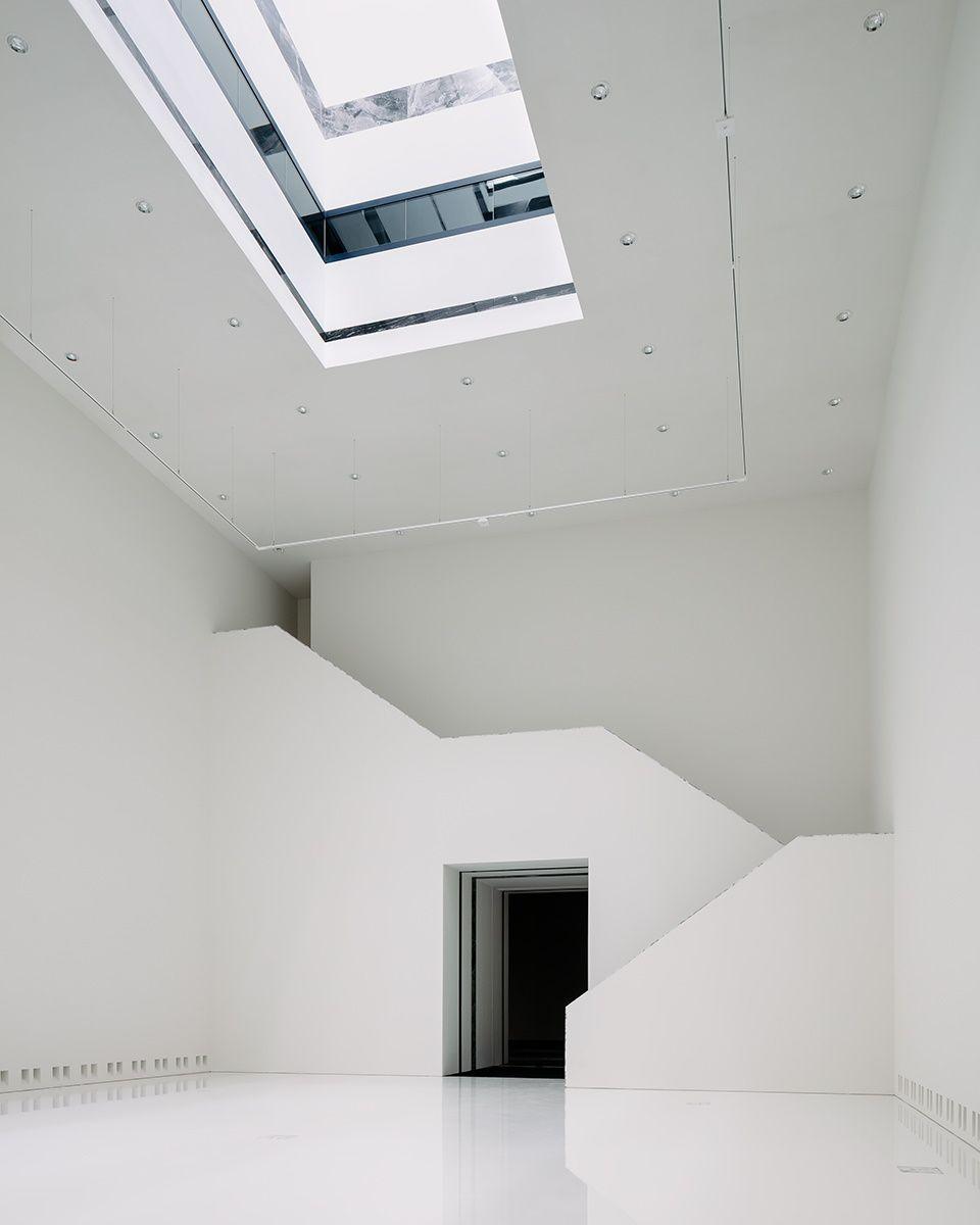Eenentwintigste-eeuwse tentoonstellingszaal met een monumentale trap die naar de hoger gelegen tentoonstellingszalen leidt. Bovenaan, één van de vier lichtvallen die de ruimte verticaal verbindt met de derde verdieping en de daklichten.