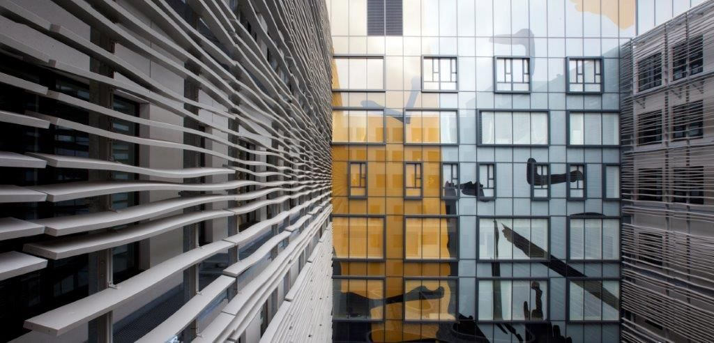 De zonweringlamellen optimaliseren de daglichtinval via hun lichte inclinatie en maken een visuele golfbeweging die het gebouw een markante uitstraling geeft. (Foto: Philippe Van Gelooven)