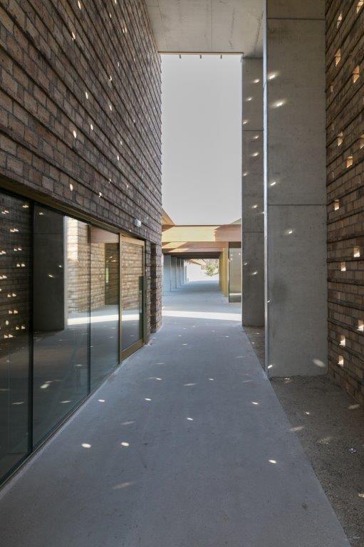 De gevel is ingevuld met ruw metselwerk, dat hier en daar subtiele openingen bevat om het robuuste karakter van het gebouw enigszins te doorbreken. (Beeld: Vanhout)