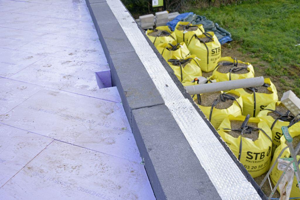 On remarque ici l'un des cônes pratiqués dans l'isolant pour l'évacuation des eaux de pluie. Les sacs de graviers, en contrebas, sont prêts à être déversés sur la toiture.