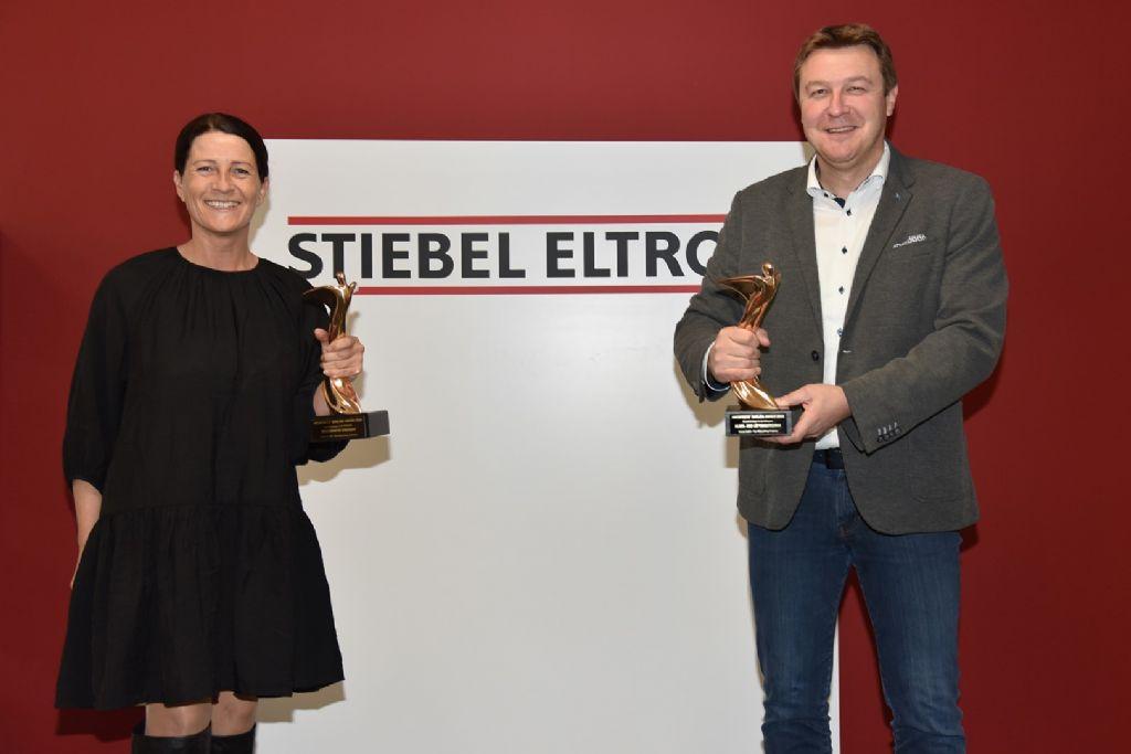 """Reclamemanager Fátima Freitas en persvoorlichter Henning Schulz met de twee """"Oscars van de bouwsector"""" die STIEBEL ELTRON dit jaar won in de categorieën """"Hernieuwbare energieën"""" en """"Ventilatie en klimaatregeling""""."""