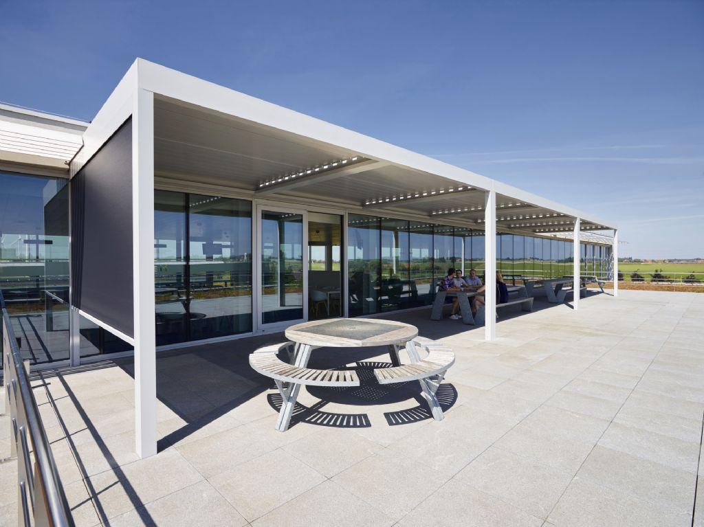 Algarve terrasoverkappingen van Renson houden met hun dakstructuur als 'luifel boven de ramen' niet alleen het invallend zonlicht tegen maar zorgen er ook voor dat medewerkers over de middag op een aangename manier buiten kunnen lunchen.