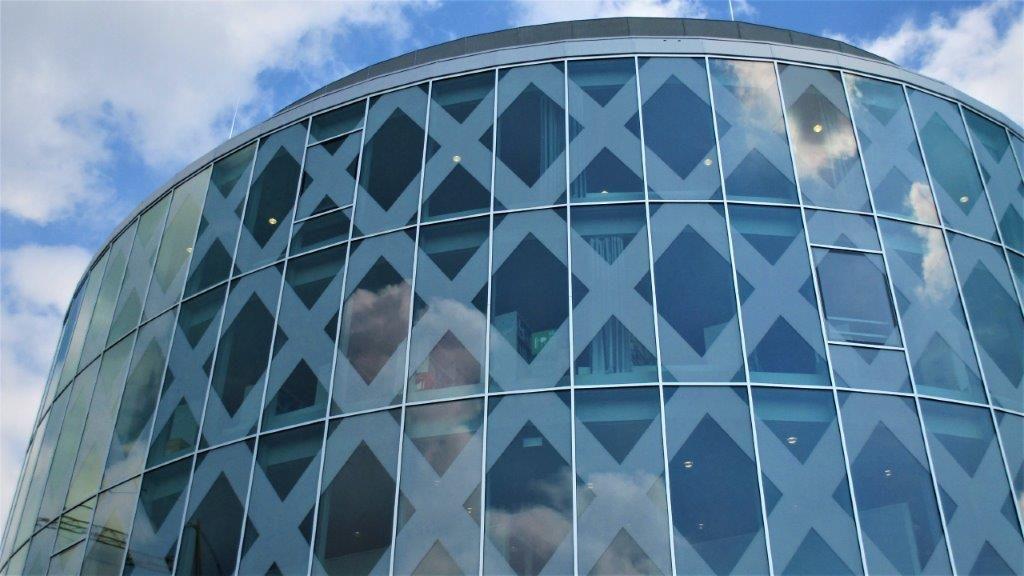 De bibliotheektoren heeft een ellipsvorm en bestaat uit een staalconstructie met gordijngevel.
