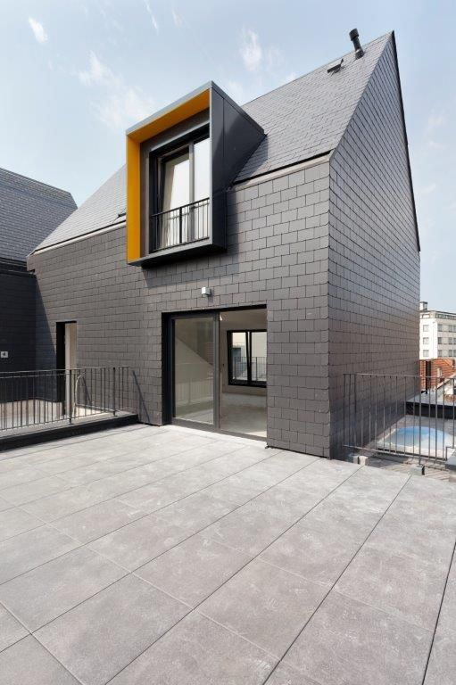 De duplexappartementen ter hoogte van de daken zijn lichtjes teruggetrokken gerealiseerd en uniform bekleed met donkergrijze vezelcementleien.