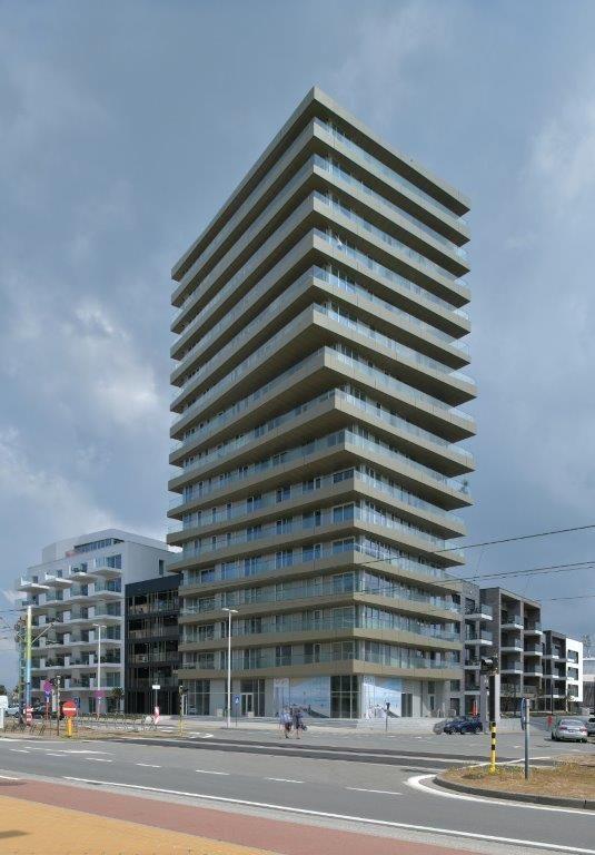 De 57 meter hoge woontoren springt sterk in het oog dankzij zijn markante torsie in de buitengevel en de betonnen structuur.