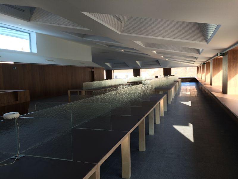 De leeszaal omhult met zijn donkere warme houten afwerking de intieme studieplekken en kan plaats bieden aan 124 lezers