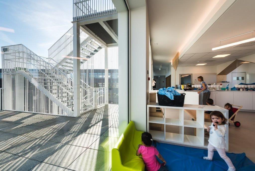 De leef- en verzorgingsruimtes zijn uitgerust met hoge ramen die starten op vloerniveau, zodat er steeds voldoende natuurlijk licht binnenvalt en de kinderen zelfs in lig- of zithouding zicht hebben op de buitenwereld. (Beeld: Yoni De Mulder)