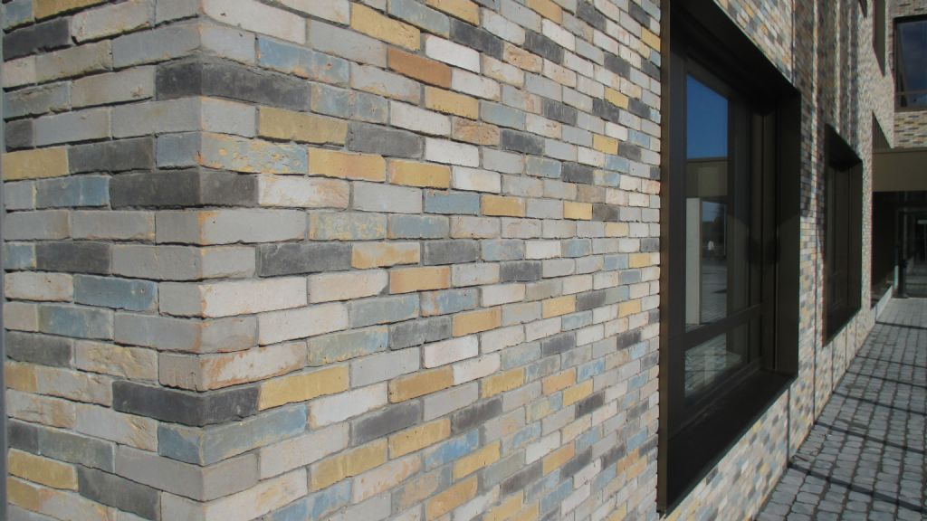 De rafelige ruimtelijke context van de omliggende bebouwing was mee bepalend voor de differentiatie in de buitencontouren en de contrasten in de gevels, die bestaan uit een gemengde baksteensamenstelling en bronskleurig schrijnwerk. (Beeld: Tim Janssens)